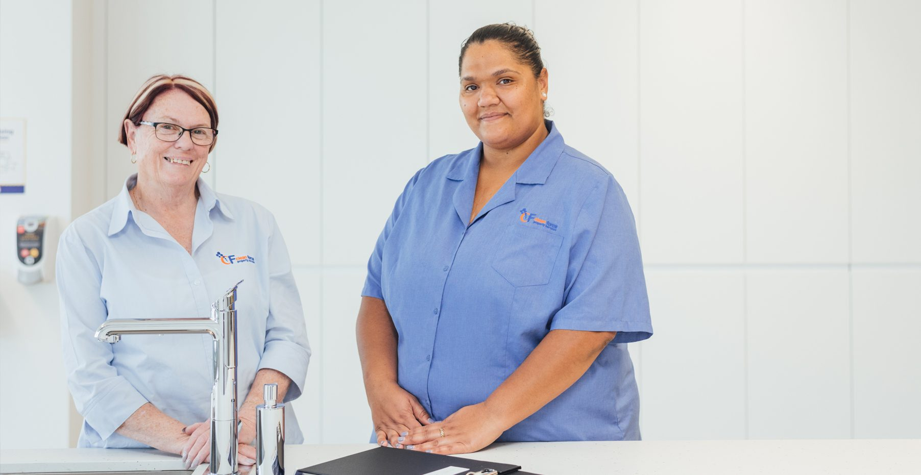 Rhonda and Nakoa stand in their Clean Force Uniforms in a meeting room.
